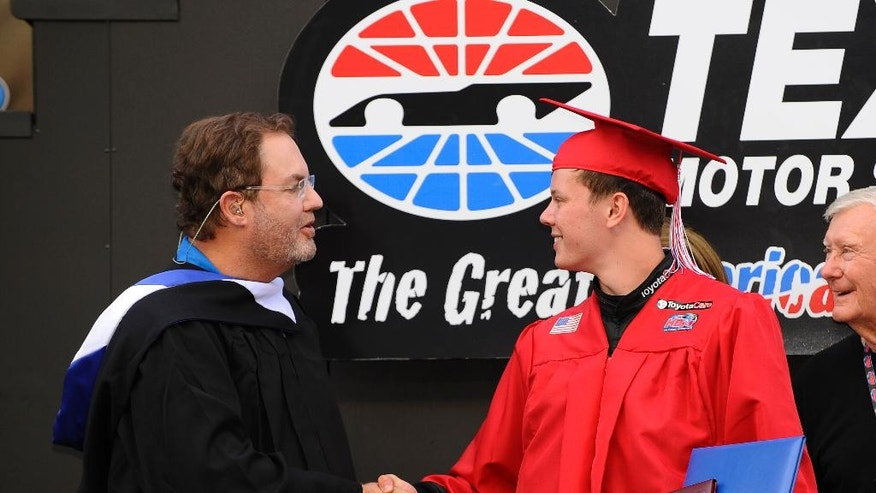 Texas Motor Speedway President Eddie Gossage, left, congratulates Erik Jones, right, as he takes part in a graduation ceremony on the stage during driver introductions for a NASCAR truck race at Texas Motor Speedway in Fort Worth, Texas, Friday, June 6, 2014. Tonight's race falls on the same day as Jone's high school senior  graduation however, he chose to forego the opportunity to walk across the stage with his fellow classmates to drive in the race. (AP Photo/Ralph Lauer)