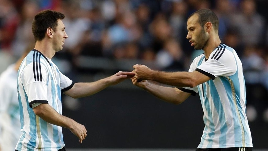 Argentina's Javier Mascherano, right, gives the captain arm band to Argentina's Lionel Messi during their international friendly soccer match in La Plata, Argentina, Saturday, June 7, 2014. Argentina's team is leaving June 9 for Brazil to compete in the World Cup. (AP Photo/Natacha Pisarenko)