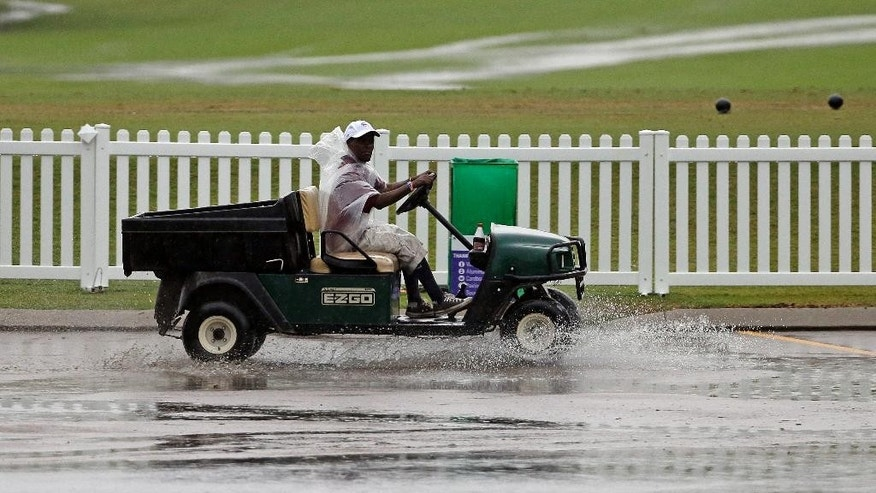 A worker drives a golf cart through standing water during a weather delay at the second round of the St. Jude Classic golf tournament Friday, June 6, 2014, in Memphis, Tenn. (AP Photo/Mark Humphrey)