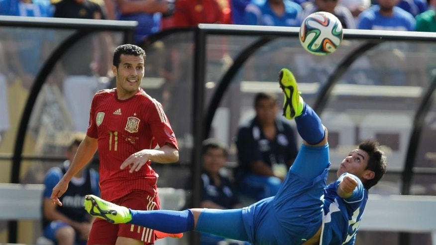 El Salvador's Alexander Larin (13) makes on overhead kick as Spain's Pedro Rodriguez (11) defends during the first half of an exhibition soccer game, Saturday, June 7, 2014, in Landover, Md. (AP Photo/Luis M. Alvarez)