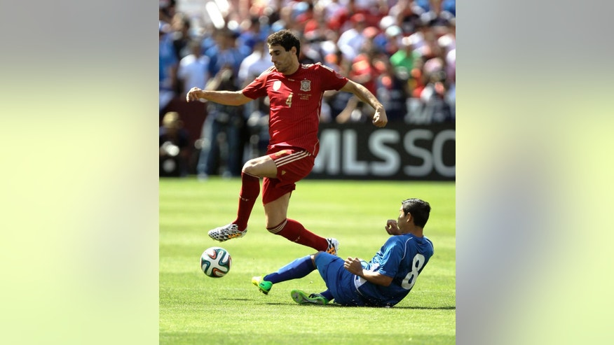 Spain's Javi Martinez (4) controls the ball as El Salvador's Keven Santamaria (8) defends during the first half of an exhibition soccer game, Saturday, June 7, 2014, in Landover, Md.. (AP Photo/Luis M. Alvarez)