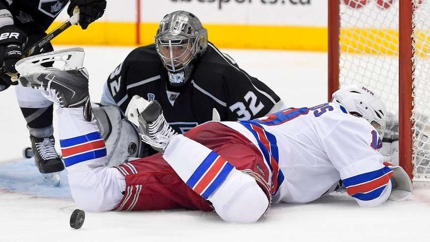 goalie Jonathan Quick, top, blocks a shot by New York Rangers defenseman Marc Staal during the third period of Game 2 in the NHL Stanley Cup Final hockey series in Los Angeles, Saturday, June 7, 2014. (AP Photo/Mark J. Terrill)