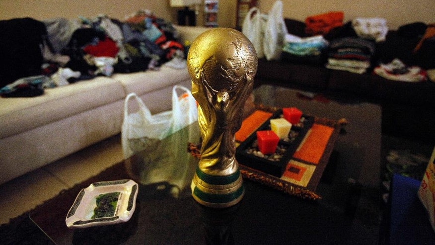A replica of the World Cup trophy sits on a table at the home of Chile soccer fan Cristian Uribarri as he packs to travel to Brazil for the tournament, in Santiago, Chile, late Thursday June 5, 2014. Cristian Uribarri and four friends are traveling from Chile in a wood-framed, aluminum-sided trailer he built from scratch. (AP Photo/Luis Hidalgo)