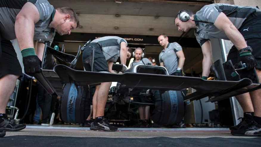 Mechanics slip on the nose cone on the car of Mercedes driver Lewis Hamilton from Great Britain during the third practice session at the Canadian Grand Prix Saturday, June 7, 2014 in Montreal. (AP Photo/The Canadian Press, Paul Chiasson)