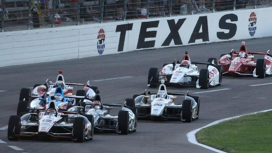 Pole-sitter Will Power (12) leads the pack at the start of the IndyCar auto race at Texas Motor Speedway in Fort Worth, Texas, Saturday, June 7, 2014. (AP Photo/Tim Sharp)