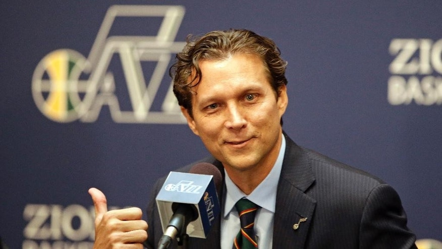 Quin Snyder gestures fter being introduced as the new Utah Jazz head coach during an NBA basketball news conference Saturday, June 7, 2014, in Salt Lake City. The Jazz announced Friday that they hired the Atlanta Hawks assistant coach to replace Tyrone Corbin, who was let go earlier this year after three-plus seasons in Salt Lake City.  (AP Photo/Rick Bowmer)