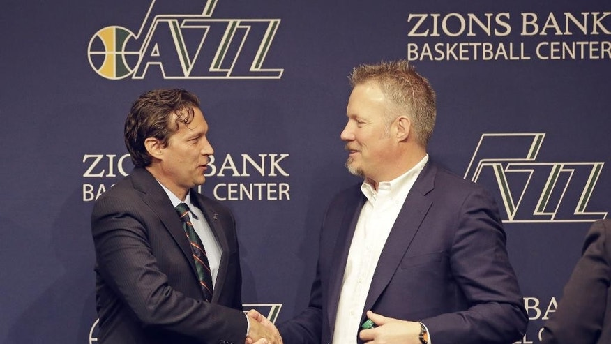 Quin Snyder, left, receives a hand shake from Utah Jazz CEO Greg Miller after being introduced as the new Utah Jazz head coach during a news conference Saturday, June 7, 2014, in Salt Lake City. The Utah Jazz announced Friday that they have hired Atlanta Hawks assistant coach Snyder to replace Tyrone Corbin, who was let go earlier this year after three-plus seasons in Salt Lake City. Snyder most recently completed his first season as an assistant with Atlanta. He has also been an assistant with the Los Angeles Lakers, the Philadelphia 76ers and the Los Angeles Clippers.  (AP Photo/Rick Bowmer)