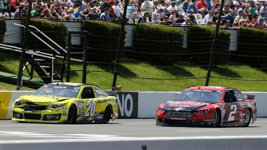Driver Brad Keselowski (2) passes a damaged Matt Kenseth (20) during the NASCAR Sprint Cup series Pocono 400 auto race, Sunday, June 8, 2014, in Long Pond, Pa. (AP Photo/Mel Evans)