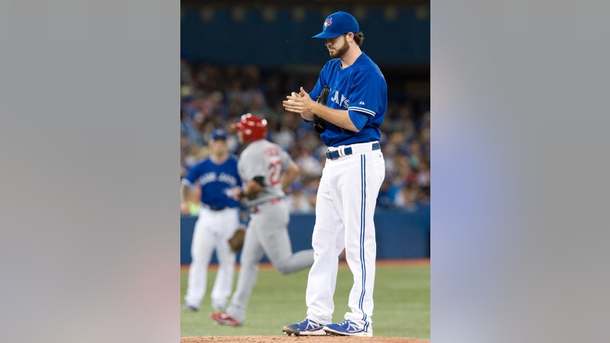 Toronto Blue Jays starting pitcher Drew Hutchison reacts on the mound as St. Louis Cardinals Jhonny Peralta rounds the bases on his solo homer during the third inning of a baseball game in Toronto on Sunday June 8, 2014. (AP Photo/the Canadian Press, Frank Gunn)