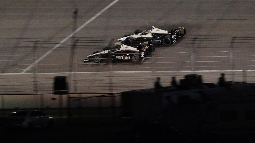 Ed Carpenter (20) starts to pass Will Power (12) for the lead  during an IndyCar auto race at Texas Motor Speedway in Fort Worth, Texas, Saturday, June 7, 2014. Carpenter went on to win the race. (AP Photo/Ralph Lauer)