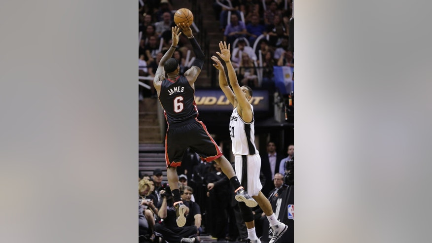 Miami Heat forward LeBron James (6) shoots as San Antonio Spurs forward Tim Duncan (21) defends during the second half in Game 2 of the NBA basketball finals on Sunday, June 8, 2014, in San Antonio. (AP Photo/Eric Gay)