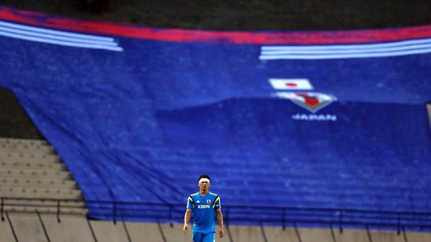 Japan's Shinji Okazaki walks in front of giant Japanese team uniform hanging in the stands during a training session in Sorocaba, Brazil, Sunday, June 8, 2014.  Japan plays in group C of the 2014 soccer World Cup. (AP Photo/Shuji Kajiyama)