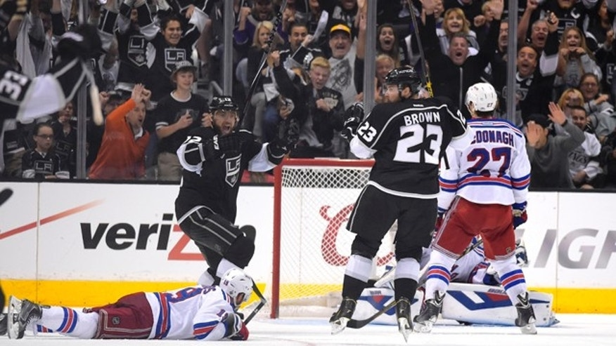 June 7, 2014: Los Angeles Kings right wing Dustin Brown, third from right, celebrates with right wing Marian Gaborik, second from left, of Slovakia, after scoring the game-winning goal as New York Rangers center Brad Richards, left, lies on the ice and defenseman Ryan McDonagh, right, reacts during the second overtime period in Game 2 of the Stanley Cup Final in Los Angeles. The Kings won 5-4.