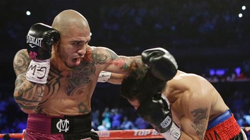 Miguel Cotto, left, of Puerto Rico, fights Sergio Martinez, of Argentina, during the first round of the WBC middleweight title boxing match Saturday, June 7, 2014, in New York.  (AP Photo/Frank Franklin II)
