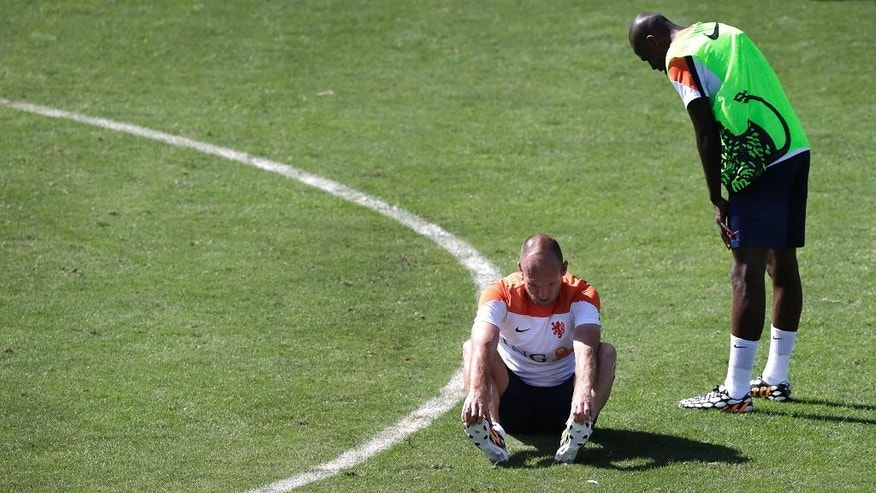 Arjen Robben, left, sits on the ground after being tackled by Bruno Martins Indi, right, both from the Netherlands soccer team during a training session in Rio de Janeiro, Brazil, Sunday June 8, 2014. Arjen Robben has reacted angrily to a tough challenge from Netherlands teammate Bruno Martins Indi during a World Cup training session at their base in Rio. The Netherlands play in group B of the 2014 soccer World Cup. (AP Photo/Wong Maye-E)