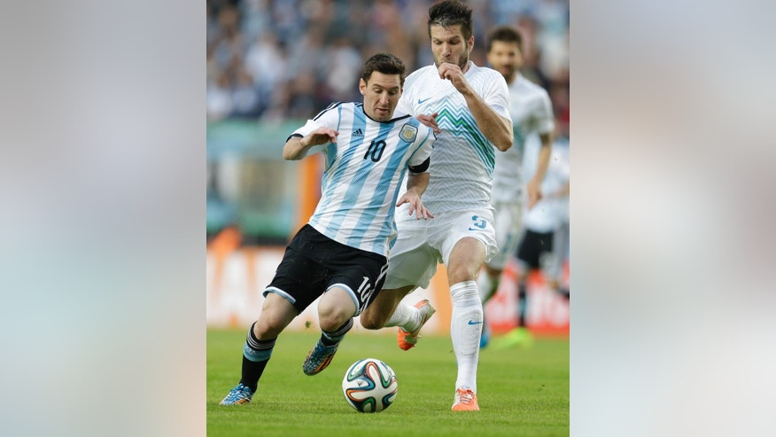 Argentina's Lionel Messi, left, fights for the ball with Slovenia's Bostjan Cesar during their international friendly soccer match in La Plata, Argentina, Saturday, June 7, 2014. Argentina's team is leaving June 9 for Brazil to compete in the World Cup. (AP Photo/Natacha Pisarenko)