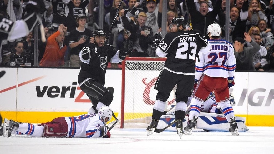 Los Angeles Kings right wing Dustin Brown, third from right, celebrates with right wing Marian Gaborik, second from left, of Slovakia, after scoring the game-winning goal as New York Rangers center Brad Richards, left, lies on the ice and defenseman Ryan McDonagh, right, reacts during the second overtime period in Game 2 of the NHL hockey Stanley Cup Finals, Saturday, June 7, 2014, in Los Angeles. The Kings won 5-4. (AP Photo/Mark J. Terrill)