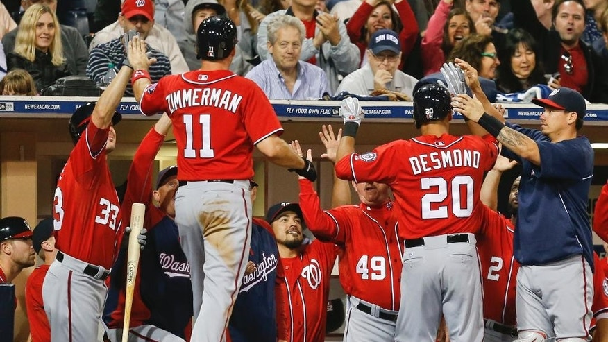 Washington Nationals' Ian Desmond and Ryan Zimmerman are congratulated at the dugout after Desmond's two-run home run against the San Diego Padres during the seventh inning of a baseball game Saturday, June 7, 2014, in San Diego. (AP Photo/Lenny Ignelzi)