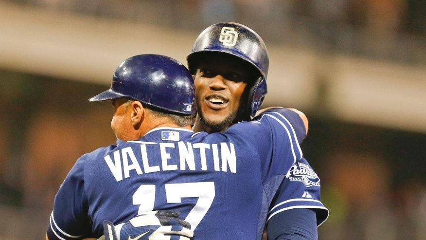San Diego Padres' Cameron Maybin is hugged by coach Jose Valentin after his game winning single in the bottom of the 12th inning gave the Padres a 4-3 victory over the Washington Nationals in a baseball game Saturday, June 7, 2014, in San Diego. (AP Photo/Lenny Ignelzi)