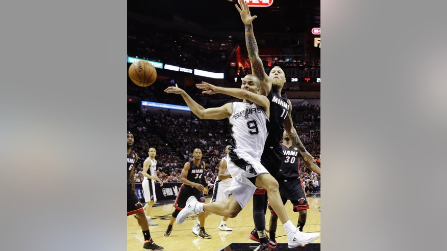 San Antonio Spurs guard Tony Parker (9) passes the ball away from Miami Heat forward Chris Andersen (11) during the first half in Game 2 of the NBA basketball finals on Sunday, June 8, 2014, in San Antonio. (AP Photo/Eric Gay)