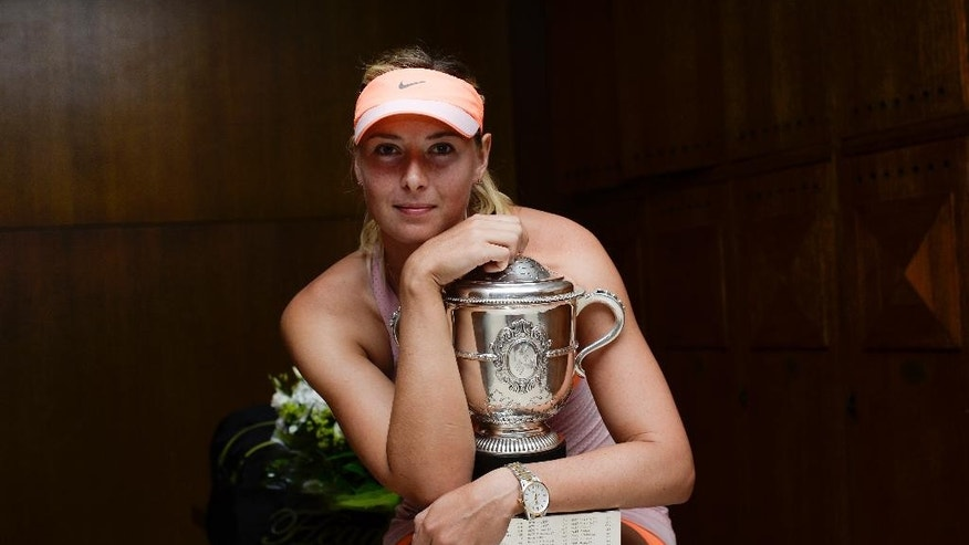 Russia's Maria Sharapova holds the trophy  as she poses for a portrait in the locker room after winning the final of the French Open tennis tournament against Romania's Simona Halep at the Roland Garros stadium, in Paris, France, Saturday, June 7, 2014. Sharapova won in three sets 6-4, 6-7, 6-4. (AP Photo/FFT/Sindy Thomas, Pool)