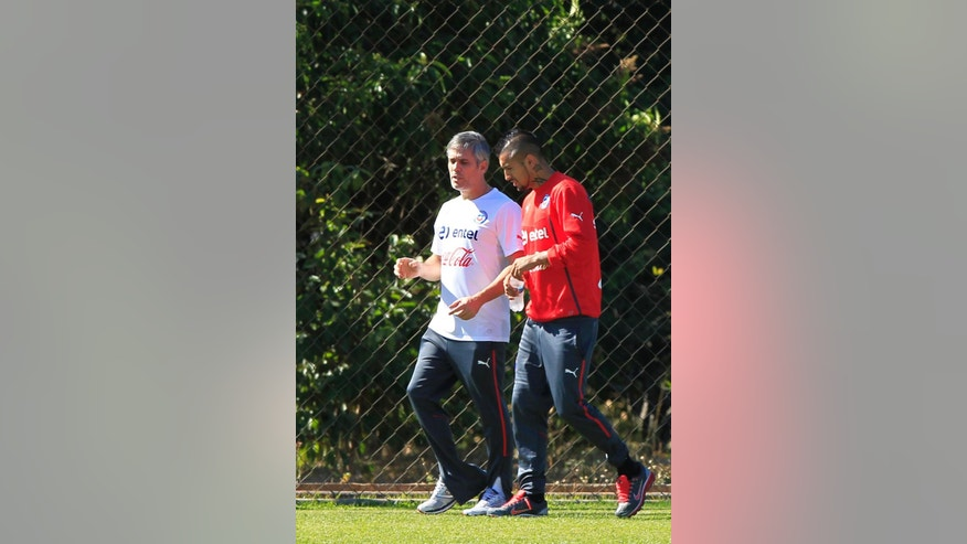 Chile's Arturo Vidal, right, walks with physical therapist Jose Amador, during a training session at Toca da Raposa 2, in Belo Horizonte, Brazil, Monday, June 9, 2014. Vidal, who is recovering from an injury, did not train. Chile will play in group B of the Brazil 2014 World Cup. (AP Photo/Bruno Magalhaes)