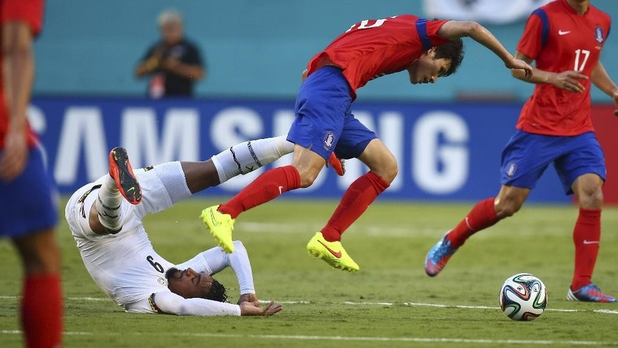Ghana's Kevin-Prince Boateng (9) and South Korea's Daesung Ha (15) battle for the ball  during the first half of an international  friendly soccer match in Miami Gardens, Fla., Monday, June 9, 2014. ( AP Photo/J Pat Carter)