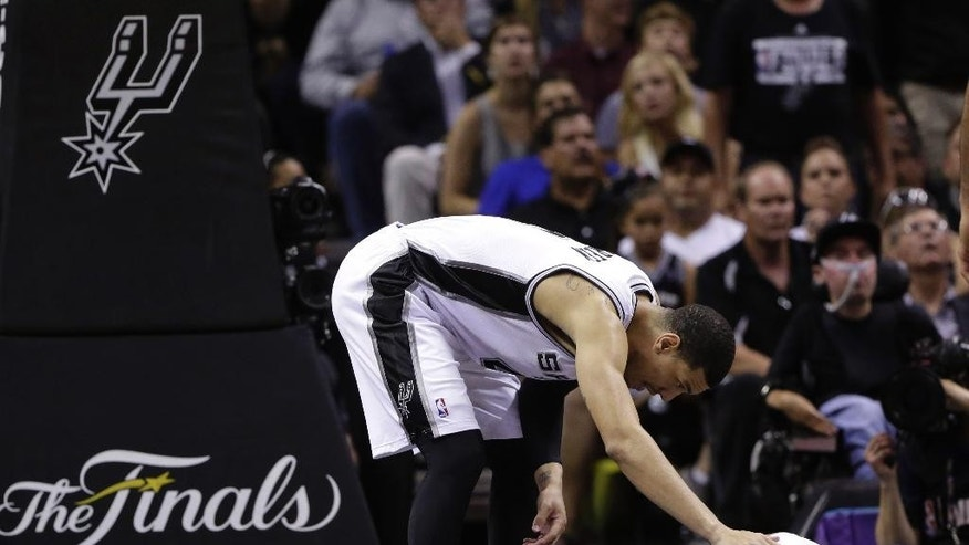 San Antonio Spurs forward Tim Duncan, left, checks on guard Tony Parker during the second half in Game 2 of the NBA basketball finals against the Miami Heat on Sunday, June 8, 2014, in San Antonio. Miami won 98-96. (AP Photo/Eric Gay)