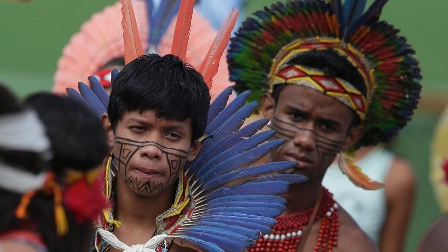 Brazilian Indians watch Germany's national soccer team at a training session near Porto Seguro, Brazil, Monday, June 9, 2014. Germany will play in group G of Brazil's 2014 soccer World Cup. (AP Photo/Matthias Schrader)