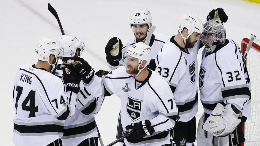 Los Angeles Kings center Jeff Carter (77) and goalie Jonathan Quick (32) are congratulated by teammates after the Kings beat the New York Rangers 3-0 in Game 3 of the NHL hockey Stanley Cup Final, Monday, June 9, 2014, in New York. (AP Photo/Frank Franklin II)