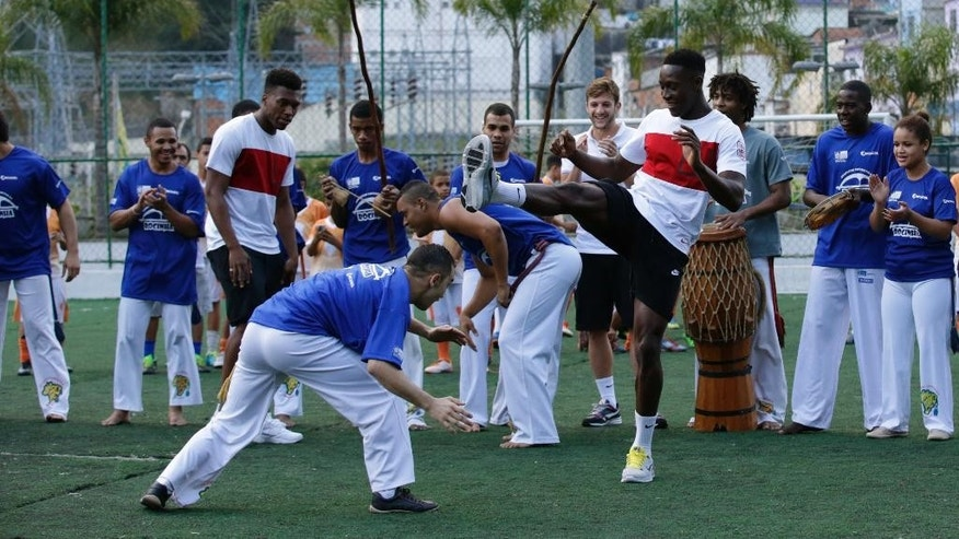 England national soccer team players Danny Welbeck, center right, and Daniel Sturridge, center left, join in a Capoeira dance demonstration with locals during a visit by a five England players to the Rocinha Sports Complex on the edge of the Rocina favela in Rio de Janeiro, Brazil, Monday, June 9, 2014.  The England soccer team are staying in Rio de Janeiro as their base city for the 2014 soccer World Cup.  (AP Photo/Matt Dunham)