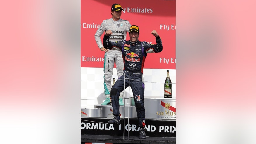 Red Bull driver Daniel Ricciardo, from Australia, celebrates in front of Mercedes driver Nico Rosberg, from Germany, after winning the Canadian Grand Prix Sunday, June 8, 2014, in Montreal. Rosberg finished second. (AP Photo/David J. Phillip)