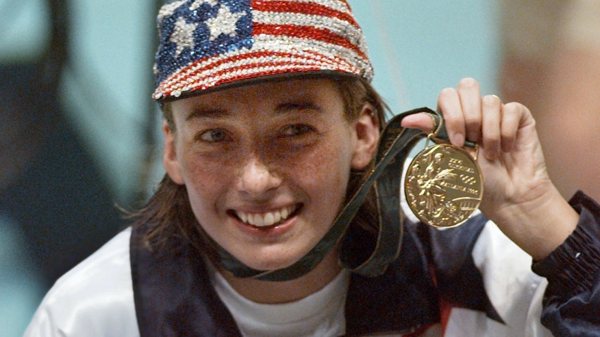 FILE: Olympic gold medalist Amy Van Dyken holds her medal after winning the women's 50 meter freestyle at the 1996 Summer Olympic Games in Atlanta.