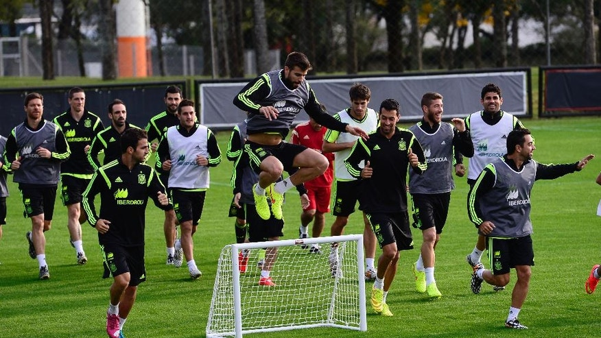 Spain's Gerard Pique, center, jumps over a mini soccer goal during a training session at the Atletico Paranaense training center in Curitiba, Brazil, Monday, June 9, 2014. Spain will play in group B of the Brazil 2014 soccer World Cup. (AP Photo/Manu Fernandez)