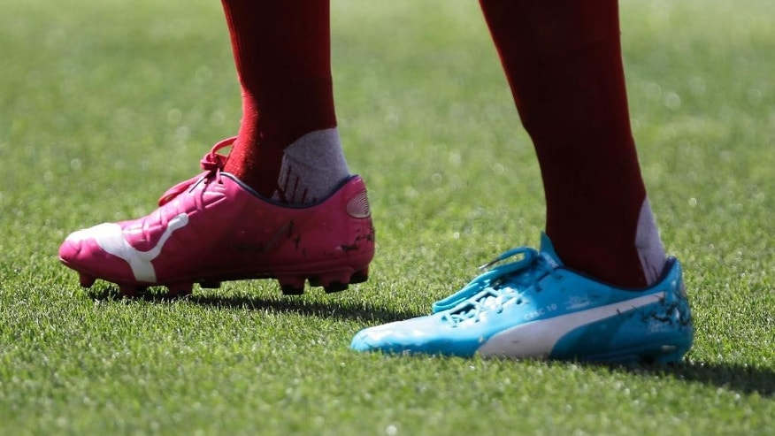 In this June 7, 2014 photo, Spain's Cesc Fabregas wears his new Puma cleats during the first half of an exhibition soccer game against El Salvador in Landover, Md. The competition on the pitch in has yet to start, but the fight over World Cup consumers is already intense _ and no more so than between the athletic companies that are jockeying for their once-every-four-years shot at the ever-growing soccer market(AP Photo/Luis M. Alvarez)