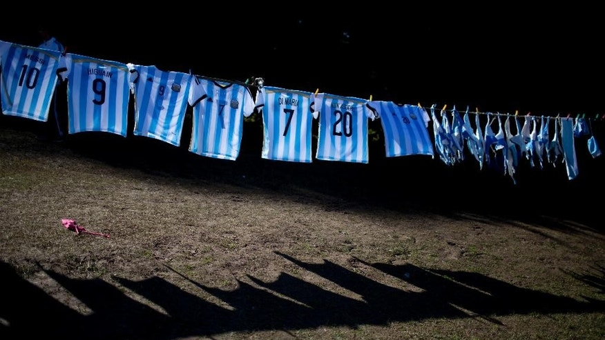 Argentina's national soccer team T-shirts hang for sale outside the Argentine Soccer Association before the team heads the airport in Buenos Aires, Argentina, Monday, June 9, 2014. Argentina's team is leaving Monday to compete in the Brazil's 2014 soccer Word Cup. (AP Photo/Natacha Pisarenko)