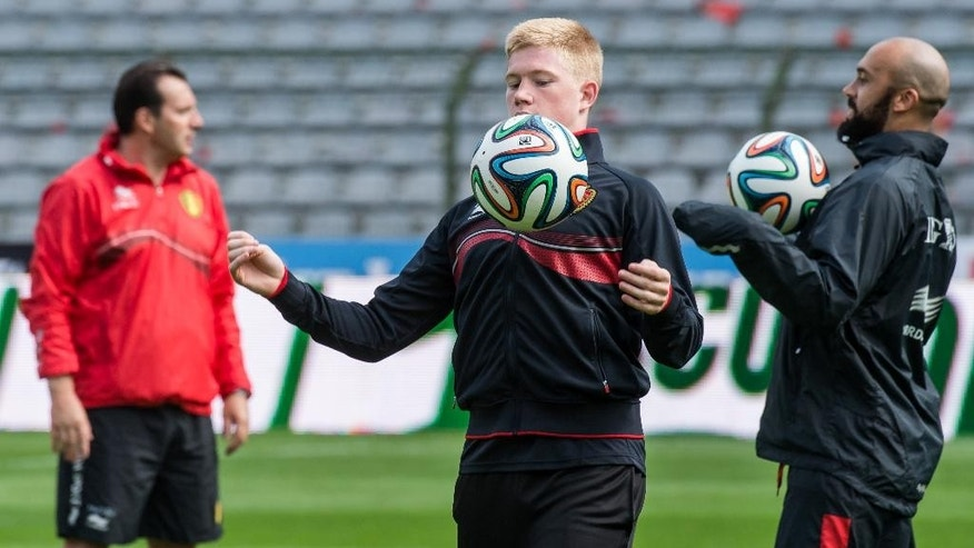 Belgium's national soccer team players Kevin De Bruyne, center, and Anthony Vanden Borre, right, practice during their last training in Belgium before leaving for Brazil at the King Baudouin stadium in Brussels, Sunday June 8, 2014. Belgium will play against South Korea, Russia and Algeria in Group H of the World Cup 2014 in Brazil. (AP Photo/Geert Vanden Wijngaert)