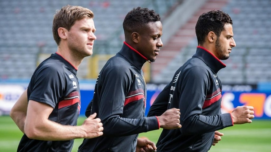 Belgium's national soccer team players Jan Vertonghen, left, Divock Origi, center, and Nacer Chadli warm up during their last training in Belgium before leaving for Brazil at the King Baudouin stadium in Brussels, Sunday June 8, 2014. Belgium will play against South Korea, Russia and Algeria in Group H of the World Cup 2014 in Brazil. (AP Photo/Geert Vanden Wijngaert)