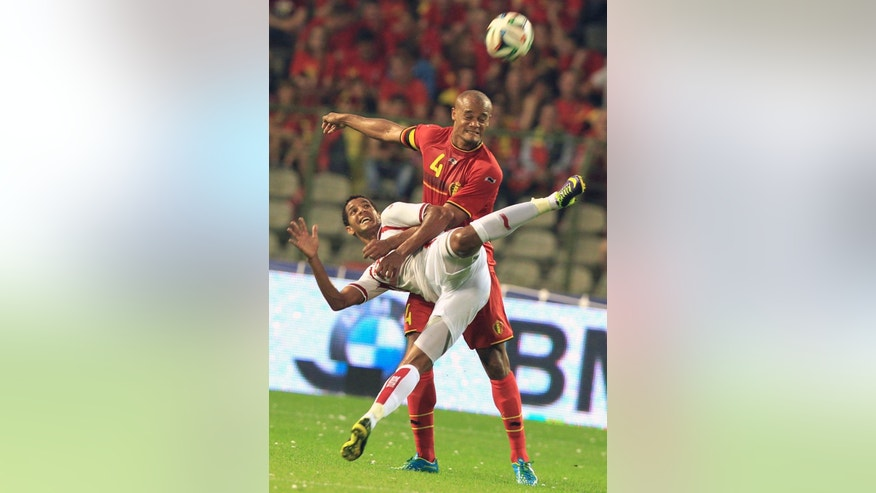Tunisia's Issam Jemaa, left, is challenged by Belgium's Vincent Kompany, during a friendly soccer match at the King Baudouin stadium in Brussels, Saturday, June 7, 2014.  Belgium will play against South Korea, Russia and Algeria in Group H of the World Cup 2014 in Brazil. (AP Photo/Yves Logghe)