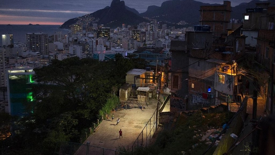 In this Tuesday, June 3, 2014 photo, kids play soccer at the Cantagalo slum in Rio de Janeiro, Brazil. Rio de Janeiro might be best known for its white sandy beaches and dramatic rocky outcroppings, but soccer pitches are just as ubiquitous a part of the World Cup city's landscape. The Two Brothers Mountain and Ipanema neighborhood are seen at top left. (AP Photo/Felipe Dana)