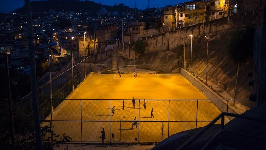 "In this Sunday, June 1, 2014 photo, youth play soccer in the Sao Carlos slum in Rio de Janeiro, Brazil. Whether professional-grade or improvised, in high-rent neighborhoods or tucked into ""favela"" hillside slums, soccer fields are literally everywhere throughout this chaotic metropolis of 12 million. (AP Photo/Felipe Dana)"