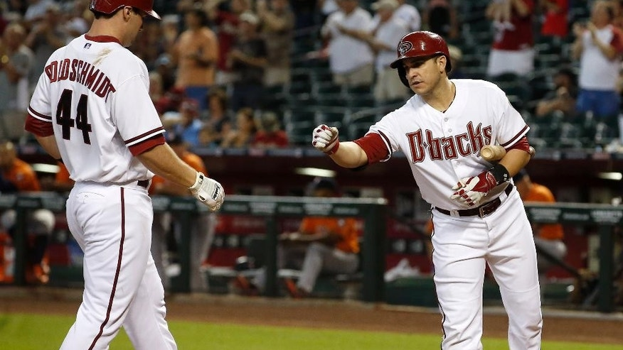 Arizona Diamondbacks' Miguel Montero, right, is ready to deliver a fist pump as Paul Goldschmidt (44) arrives at home plate after he hit a home run against the Houston Astros during the first inning of a baseball game on Tuesday, June 10, 2014, in Phoenix. (AP Photo/Ross D. Franklin)