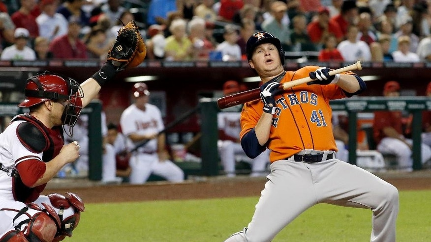 Houston Astros' Brad Peacock (41) back away from an inside pitch as Arizona Diamondbacks' Miguel Montero, left, makes the catch during the second inning of a baseball game on Tuesday, June 10, 2014, in Phoenix. (AP Photo/Ross D. Franklin)