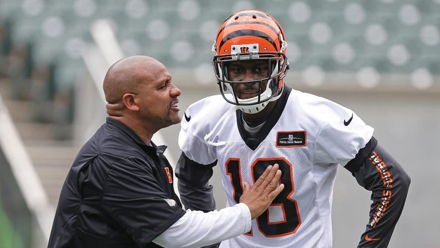 Cincinnati Bengals wide receiver A.J. Green (18) talks with offensive coordinator Hue Jackson during an NFL football mandatory minicamp, Tuesday, June 10, 2014, in Cincinnati. (AP Photo/Al Behrman)