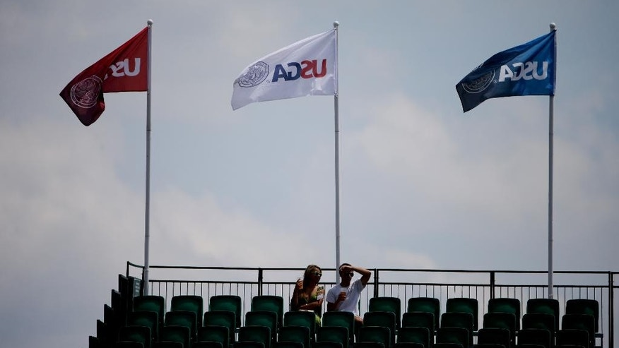 A couple on fans watch on the 18th green during a practice round for the U.S. Open golf tournament in Pinehurst, N.C., Monday, June 9, 2014. The tournament starts Thursday. (AP Photo/Chuck Burton)