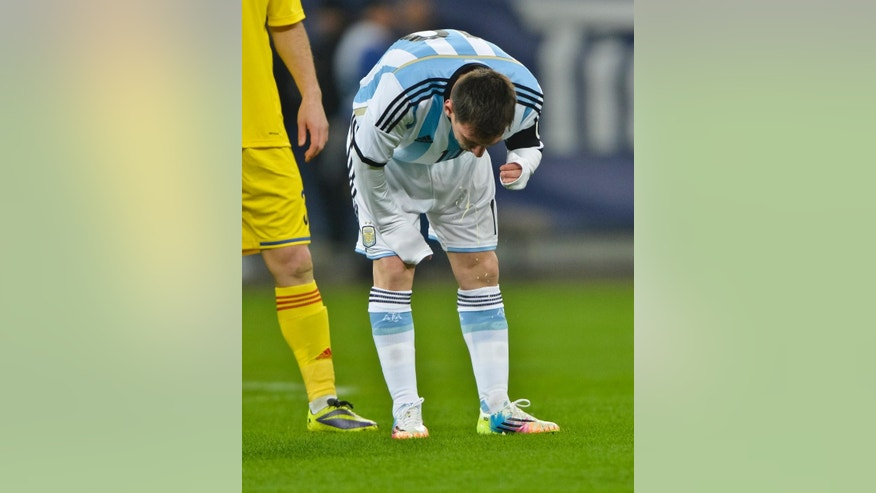 FILE - In this March 5, 2014 file photo, Argentina's Lionel Messi appears to vomit during an international friendly soccer game against Romania on the National Arena stadium in Bucharest, Romania. Messi has vomited at least a half-dozen times with Argentina and club team Barcelona, mystifying doctors and fans alike. (AP Photo, File) ROMANIA OUT