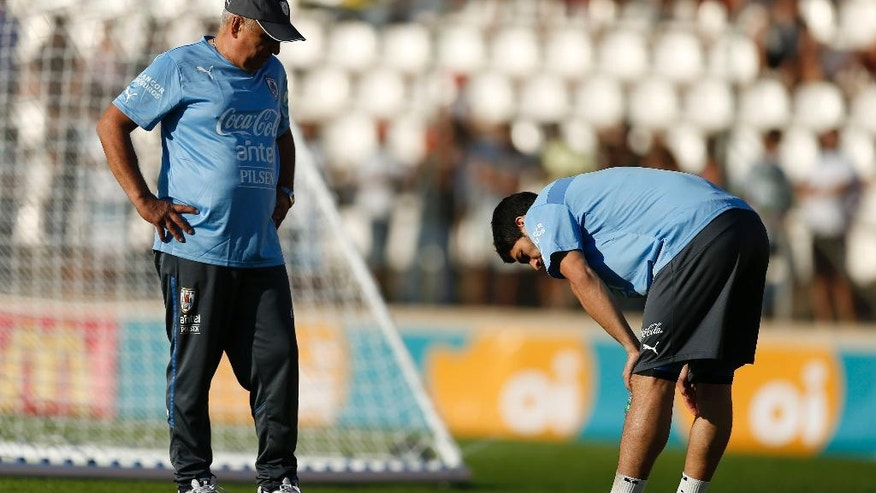 Team physical therapist Walter Ferreira, left, looks at Uruguay's Luis Suarez, right, during a training session at Jacare Stadium in Sete Lagoas, Brazil, Tuesday, June 10, 2014. Uruguay's team continues their preparations for the upcoming 2014 World Cup. (AP Photo/Victor R. Caivano)