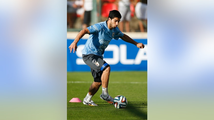 Uruguay's Luis Suarez dribbles a ball during a training session at Jacare Stadium in Sete Lagoas, Brazil, Tuesday, June 10, 2014. Uruguay continues their preparations for the upcoming 2014 World Cup. (AP Photo/Victor R. Caivano)