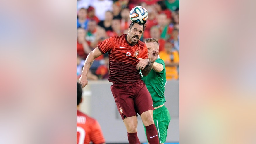 Portugal's Hugo Almeida (9) heads the ball  over Republic of Ireland's Alex Pearce during the first half of an international friendly soccer match Tuesday, June 10, 2014, in East Rutherford, N.J. (AP Photo/Bill Kostroun)