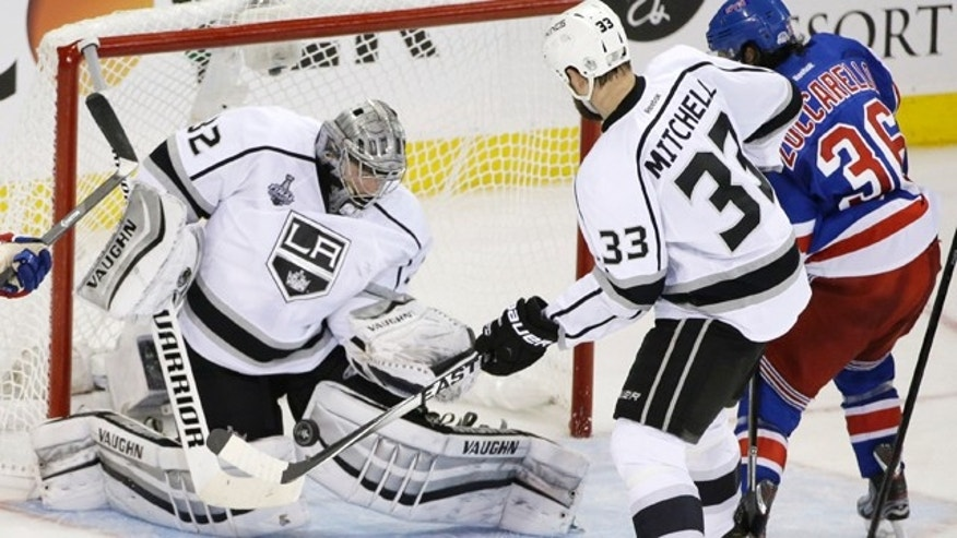 June 9, 2014: Los Angeles Kings goalie Jonathan Quick (32) blocks a shot by New York Rangers right wing Mats Zuccarello (36) as Kings defenseman Willie Mitchell (33) helps defend in the second period during Game 3 of the Stanley Cup Final. (AP Photo/Frank Franklin II)